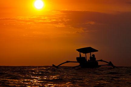Sunset at Kuta Reef. The girls are surfing. Copyright David Pu'u