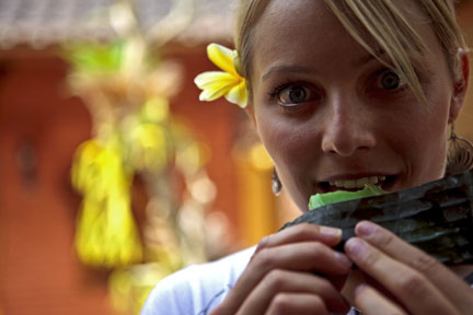 Sierra at a ceremony at Gusti's house tasting the blessed rice cakes. She is wearing the Betty B. Sea Glass drop earrings. Copyright David Pu'u